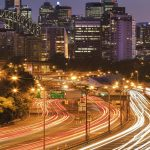 multi lane warringah freeway in Sydney against zoomed in Bridge arch and skyscraper towers at sunset. Blurred lights of headlamps and stop signals of passing cars during rush hour in big city.